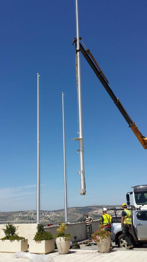 Installing 40-foot-high connie aluminum flaginis using hugs for an mda-raised exterior wall including national flags
