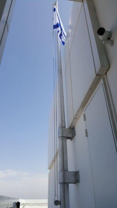 Instalación de un mástil de aluminio cono de 23 pies de altura que consta de dos unidades en el techo de un ático en Netanya