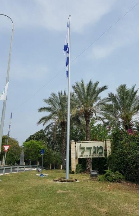 Installing תורן 40-foot steel flagpole at the eastern entrance to a tower seat